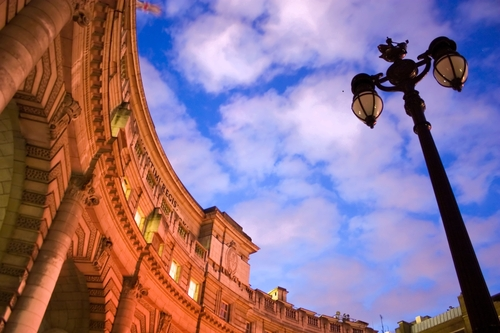 Upward view of Admiralty Arch, London, at dusk. City lights illuminate the arch beneath a vivid blue twilight sky.