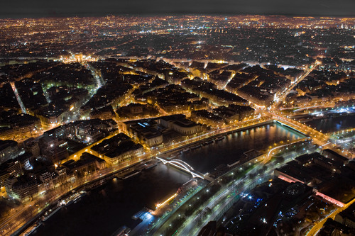 Night time view over Paris taken from the top of the Eiffel Tower. The Seine curves into the foreground beneath two illuminated bridges, while the street network can be seen leading to the Arc de Triomphe and beyond.
