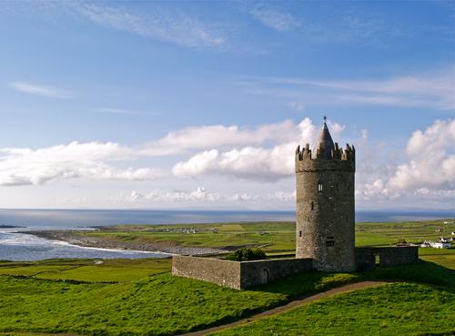 View of the Doonagore Castle overlooking Doolin and the aran islands beyond in County Clare, Ireland.