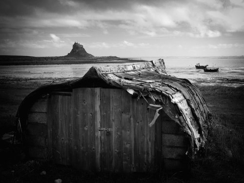 Lindisfarne castle perched on Beblowe Crag the highest point on the island viewed here from across the harbour.