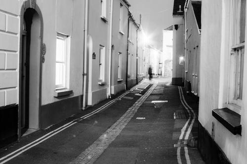 A Ghost-like figure on a lamplit street