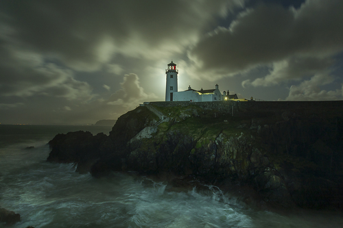 Fanad lighthouse is lit from behind by Moonlight.