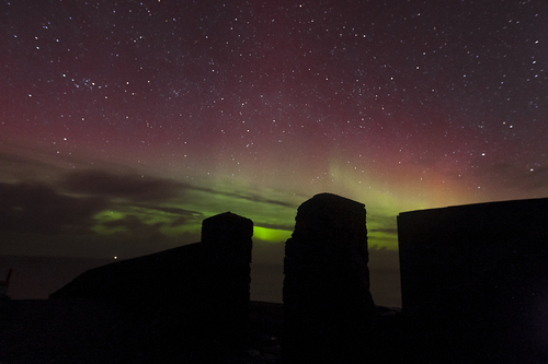 A gate post at Malin Head serves as a gateway to the Northern Lights.