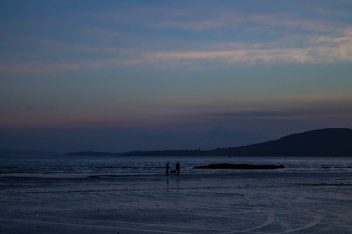 Sun sets on this couple walking their dog on Stragill Beach