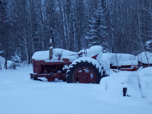 Snow covered tractor as a quiet winter evening closes in.