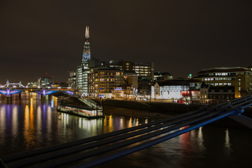 View of London along the River Thames at night. Image taken from Millennium Bridge and shows Tower Bridge, Southwark Bridge, The Shard and The Globe Theatre.