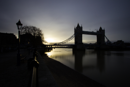 Early morning photograph catching the sunrise behind Tower Bridge in London.