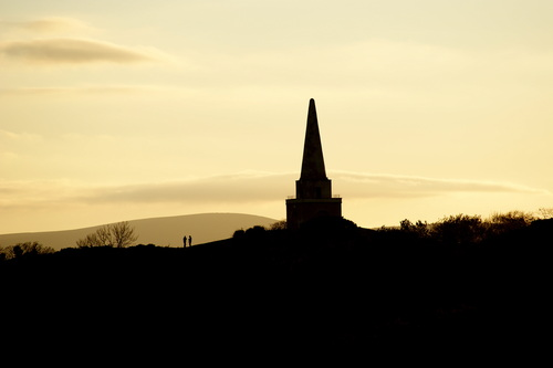 A silhouette of Killiney Hill and two hill walkers, with the sun setting behind the Dublin Mountains