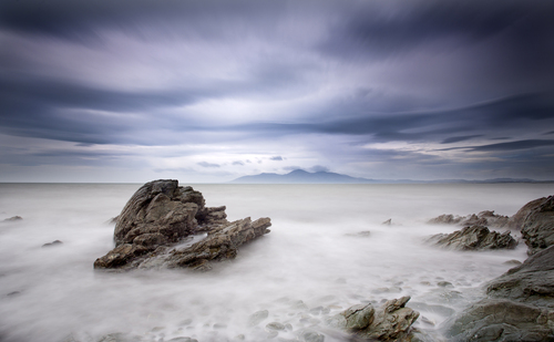 The misty sea over the shore rocks looking across Dundrum Bay towards the Mourne Mountains.
