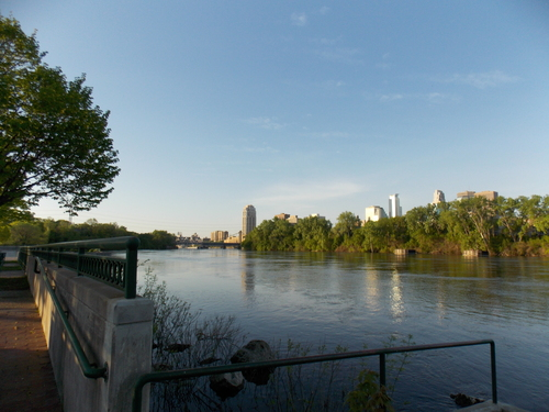 A path along the Mississippi River with the Minneapolis Skyline on the other side of the river.