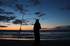 Angler fishing at Benone Beach just before sundown; Donegal in the background.