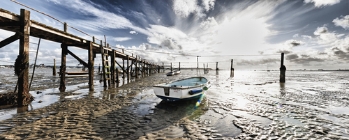 Panoramic photograph of small boats stranded at low tide by jetty in Poole, Dorset, England