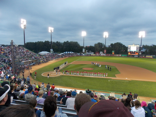 "Baseball Teams from Saint Paul, Minnesota & Winnipeg, Canada stand to attention while ""Oh Canada"" & ""The Star Spangled Banner"" are sung. This is the start of the last game, of the last series at Midway Stadium. Next year the Saints will play in the new Lowertown Ballpark."