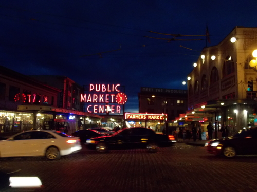 Cars passing Pike Plake Market with its famous neon signs.