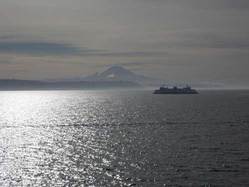 A Washington State Ferry is silhouetted against the Puget Sound and mount Rainier in the morning sun
