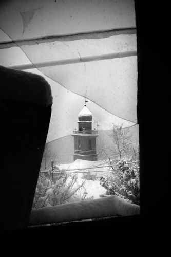 Semino's clocktower under the falling snow as seen from an abandoned house's window.