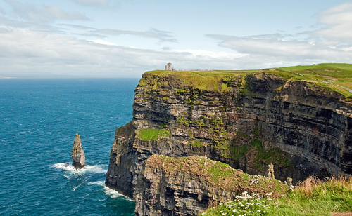 The famous Cliffs of Moher in County Clare with O'Briens Castle on the distant cliff top.  Below the Atlantic ocean crashes against the cliffs.  The Aran Islands can be seen in the distance.