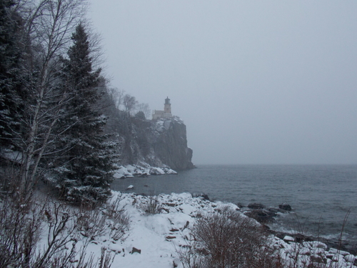 A snowy view of Split Rock Lighthouse from the lakeshore below.