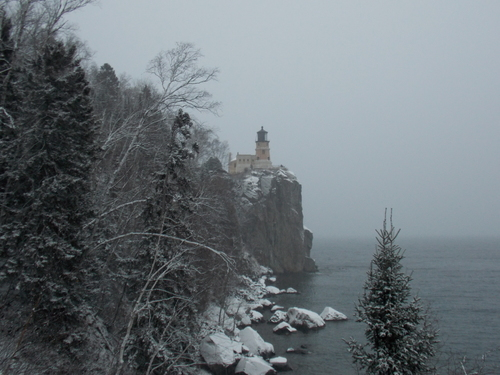 Split Rock Lighthouse looking out over Lake Superior & a snowy lakeshore.