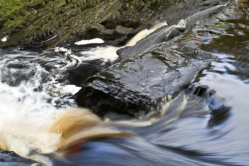 Water cascading on river rocks.