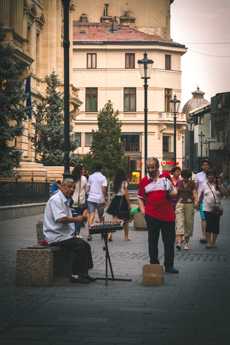 Street musician playing dulcimer on Lipscani Street in Bucharest.