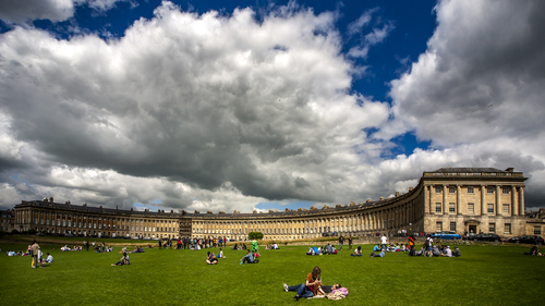 """The Royal Crescent is a row of 30 terraced houses laid out in a sweeping crescent in the city of Bath, England. Built between 1767 and 1774, it is among the greatest examples of Georgian architecture to be found in the United Kingdom.   Each original purchaser bought a length of the façade, and then employed their own architect to build a house behind the façade to their own specifications; hence what can appear to be two houses is occasionally just one. This system of town planning is betrayed at the rear and can be seen from the road behind the Crescent: while the front is uniform and symmetrical, the rear is a mixture of differing roof heights, juxtapositions and fenestration. This architecture, described as """"Queen Anne fronts and Mary-Anne backs"""", occurs repeatedly in Bath."""