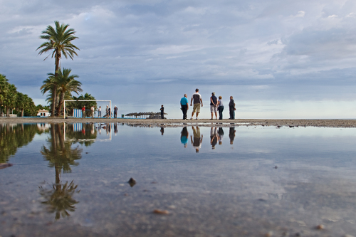 Petanque players on the beach after rain showers have left water puddles on the beach