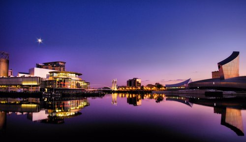 The Lowry Theatre and Imperial War Museum (North) with reflections at Salford Quays.. Manchester