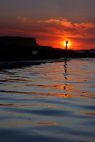 Setting sun over the eastern side of the main part of the Giants Causeway settling on the water of Dunseverick Harbour