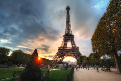 Sunset peeking over the hedge at the Eiffel Tower in Paris, France.